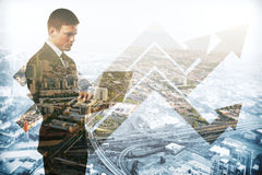 Success concept. Abstract image of caucasian businessman using laptop on city background with business charts. Double exposure. Success concept Stock Photography