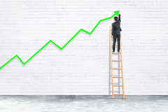 Success concept. Back view of businessman on ladder drawing upward green arrow on white brick wall. Success concept. 3D Rendering Royalty Free Stock Photo