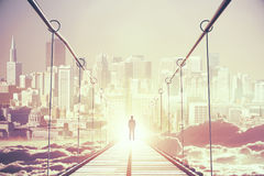 Success concept. Back view of thoughtful young businessman in the middle of bridge looking at bright city. Success concept. 3D Rendering Stock Photos