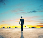 Success concept. Back view of young businessman walking on concrete ground. Beautiful sky in the background. Success concept Stock Photography