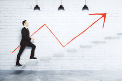 Success concept with businessman climbing the stairs and red arr Royalty Free Stock Images