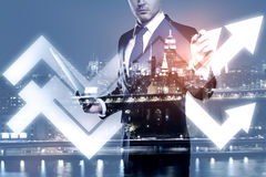 Success concept. Businessman drawing abstract upward chart arrows on night city background. Success concept. Double exposure Royalty Free Stock Photos