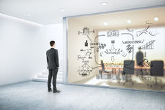 Success concept. Businessman in modern office interior with stairs looking at wall with business sketch. Success concept. 3D Rendering Stock Image