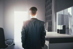 Success concept businessman in office. Success concept with businessperson standing in office interior and looking at open door with bright light. 3D Rendering Stock Image
