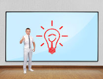 Success concept. Businessman showing thumb up and screen with lamp Royalty Free Stock Photos