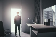 Success concept. With businessman standing in office interior and looking at open door with bright light. 3D Rendering Royalty Free Stock Image
