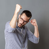 Success concept for cheerful man with beard and eyeglasses Royalty Free Stock Images