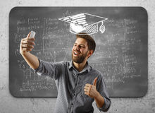 Success concept. Cheerful young businessman with drawn mortarboard taking selfie and showing thumbs up on concrete wall background with mathematical formulas on Stock Image