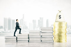 Success concept climbing book ladder. Success concept witt businessman climbing book ladder leading to golden coins and money bag on foggy city background. 3D Royalty Free Stock Photography