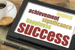 Success concept on digital tablet. Success components - happiness, significance, achievement, legacy on a digital tablet with a cup of coffee Royalty Free Stock Photo
