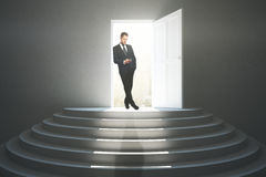 Success concept. Handsome businessman using smartphone while standing in doorway of concrete interior with stairs, city view and sunlight. Success concept. 3D Royalty Free Stock Photography