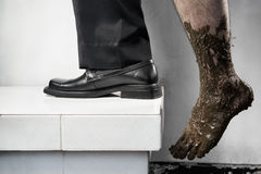Success concept from poor to be rich. One leg step from below with full of mud and the other leg using business attire. Legs of one person, without composting stock photos