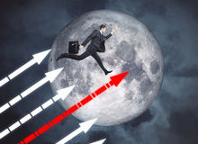 Success concept. Side view of rushing young businessman with upward chart arrows and moon in the background. Success concept. Elements of this image furnished by Stock Images
