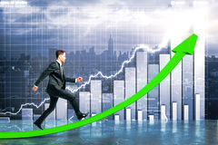 Success concept. Side view of young businessman running up green chart arrow on creative business background. Success concept Stock Photos