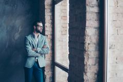 Success concept. Stylish young bearded man is standing near the. Window and looking far. He looks so classy! in a suit and glasses, with crossed hands stock image