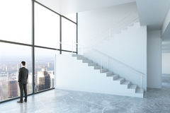 Success concept. Thoughtful businessman looking out of window in concrete interior with stairs and city view. Success concept. 3D Rendering Stock Images