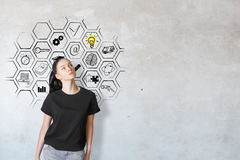 Success concept. Thoughtful caucasian female on concrete background with drawn business icons inside abstract cell mesh. Success concept Royalty Free Stock Photo