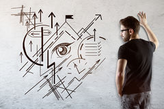 Success concept. Thoughtful young businessman looking at concrete wall with creative geometric business vision sketch. Success concept Royalty Free Stock Photo