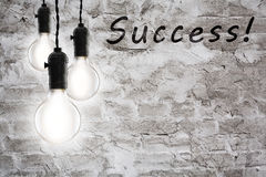 Success concept - vintage incandescent bulbs on wall background Royalty Free Stock Photo