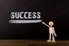 Success concept, Wooden Stick Figure pointing the word Success on a chalkboard. Blackboard royalty free stock photography