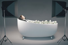 Success concept. Young businessman relaxing in bathtub filled with dollar banknote stacks, illuminated with professional lighting equipment on grey background Stock Photo