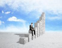 Success concept. Young businessman using laptop computer while sitting on abstract concrete chart bars with business doodles on sky background. Success concept Royalty Free Stock Image