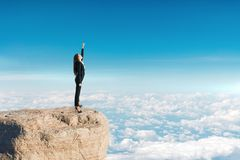 Success and confidence concept. Confident young businesswoman with raised arm standing on sky background. Success and confidence concept royalty free stock photos