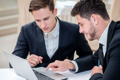 Success and confidence. Two successful and confident businessman. Sitting at the table in a business office in full costume in the office and working at a Stock Image