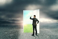 Success and dream concept. Businessman with creative opportunity door on abstract outdoor sky landscape background. Success and dream concept royalty free stock photography