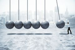 Success and effort concept. Side view of businessman pushing abstract concrete pendulum on blurry city background. Success and effort concept. 3D Rendering stock images