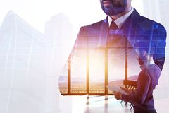 Success and employment concept. Thoughtful young businessman standing on abstract creative city office background with sunlight and copy space. Double exposure royalty free stock photos
