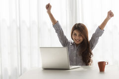 Success. Excited woman raising her arms while working on her laptop in her home Stock Photos