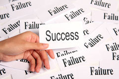 Success among failure. Hand holding paper card with success word Stock Image