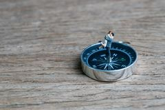 Success family guidance for bright future direction, happy miniature couple husband holding wife standing on compass on wood back stock photo