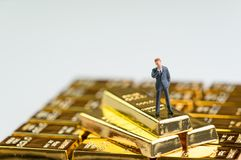 Success finance investment wealth concept, miniature figure busi. Nessman standing on stack of shiny gold bar bullions ingot Stock Images