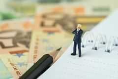 Success financial business leader concept by miniature figure bu. Sinessman as a proud leader standing on white paper notepad and pile of Euro banknotes stock photos