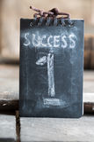 Success, first, win concept. Chalk inscription and wooden table Stock Photos