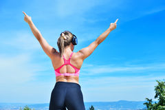 Success fitness winning woman concept with earphones. Royalty Free Stock Photo