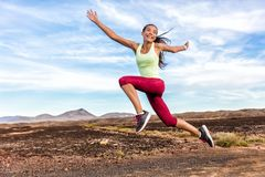 Success freedom carefree runner woman running fun. Happiness, joy, energetic athlete girl happy of weight loss goal achievement jumping funny on summer outdoor royalty free stock image