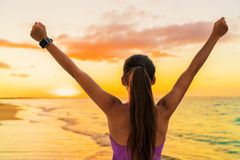 Success freedom smartwatch woman at beach sunset. Success freedom smartwatch woman from behind at sunset. Winning goal achievement fitness athlete girl cheering Stock Photos