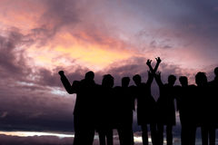 Success, friendship, community and  happiness concepts. Backlight shot of Multi-racial group of people with raised arms looking at sunset.  Success, friendship Stock Photos
