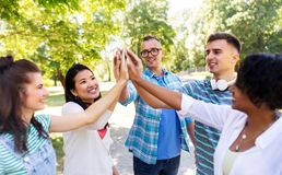 Happy friends making high five in park stock photo