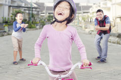 Success girl riding a bike. Portrait of successful little girl riding a bicycle with her dad and brother clapping hands on the back Stock Photography