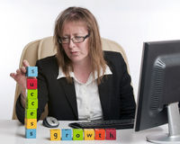 Success and growth in business. A happy and successful business woman in a business situation spelling out the words success and growth with lettered blocks Stock Images