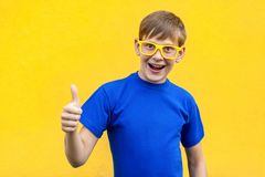 Success and happiness thumbs up, looking at camera and toothy sm. Ile. Studio shot, yellow background Stock Images