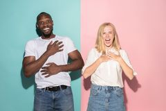 Happy afro man and woman. Dynamic image of caucasian female and afro male model on pink studio. royalty free stock photos