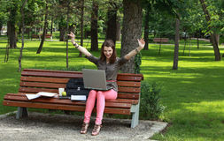 Success. Happy young woman with a laptop rising her arms up, outside in an urban park Stock Photography