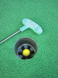 Success! Hole in One!. Yellow golf ball inside the cup with the putter laying next to it on the green at a mini golf course. Game over royalty free stock photo