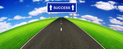 Success horizon. A highway crossing a lush green landscape towards the horizon towards success indicated by an huge 'success' road sign Stock Photos