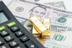 Success investment or financial wealth calculation concept, gold. Bars / ingot on pile of money US dollar banknotes with calculator Royalty Free Stock Photo